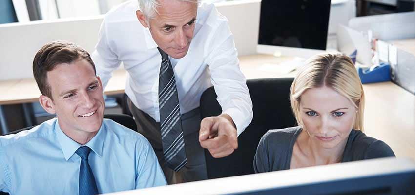 Ein Mann erklärt zwei Kolleginnen etwas am Bildschirm des Computers.