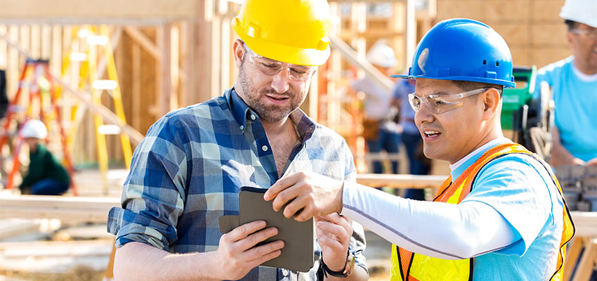 Zwei Bauarbeiter arbeiten auf der Baustelle mit einem Tablet.