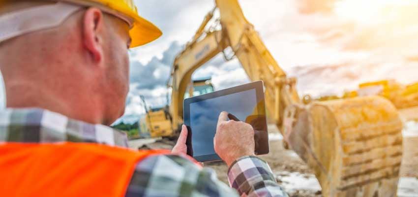 Ein Bauarbeiter, von hinten fotografiert, tippt auf einem Tablet. Im Hintergrund ist ein Bagger zu sehen.