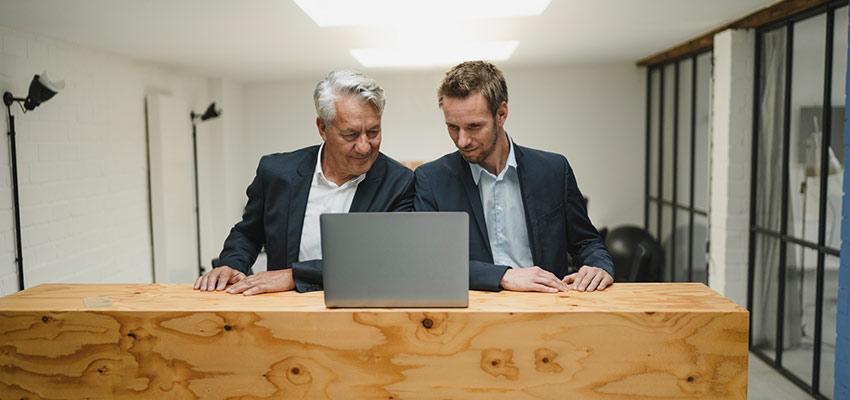 Zwei Männer im Sakko besprechen etwas vor einem Laptop.