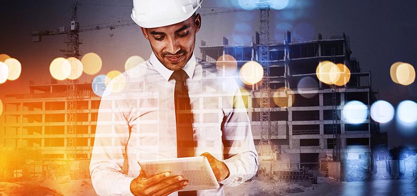 Mann mit Hemd, Schlips und Bauhelm sieht lächelnd auf ein Tablet in seiner Hand