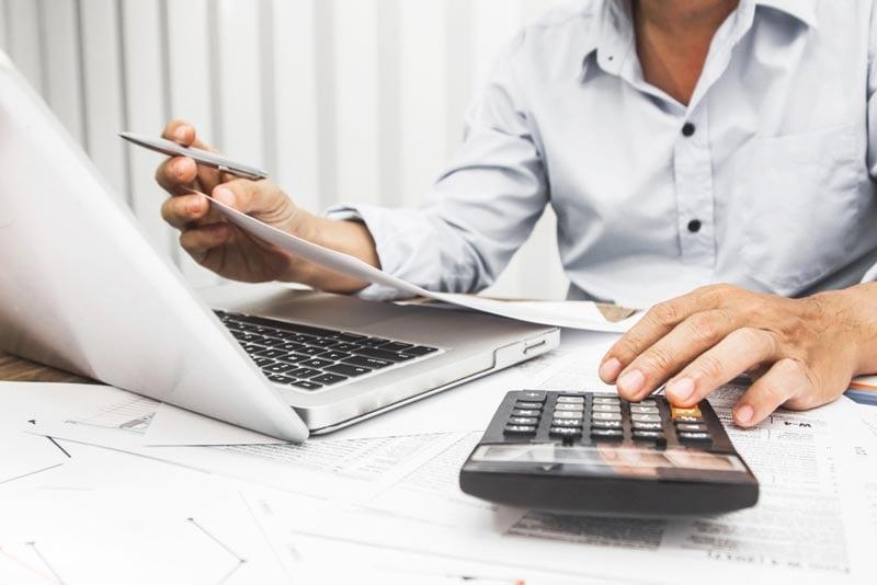 Mann sitz am Schreibtisch und arbeitet mit Laptop und Taschenrechner