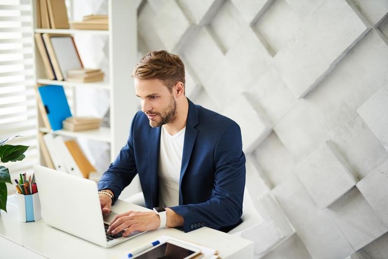 Junger Mann sitzt mit Laptop am Schreibtisch vor einer weißen Wand