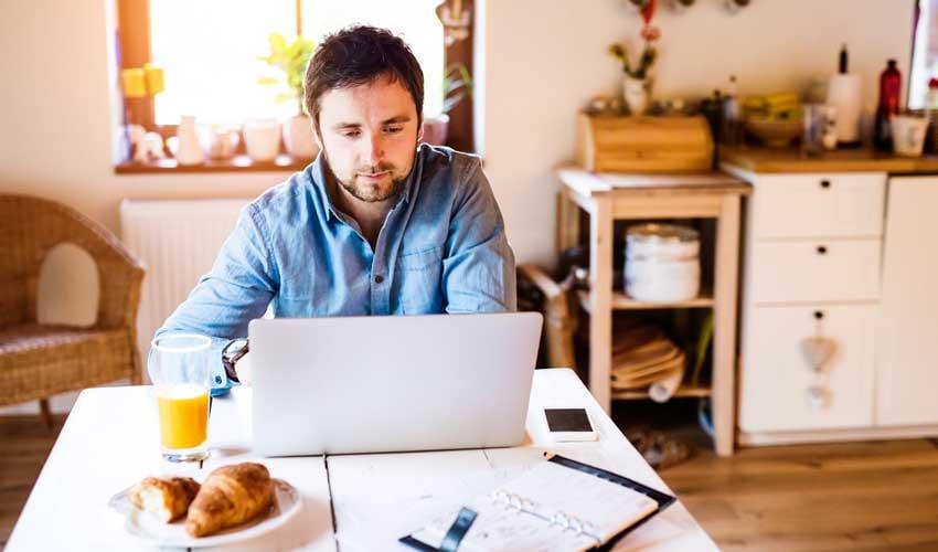 Mann sitzt am Esstisch mit Frühstück und Laptop