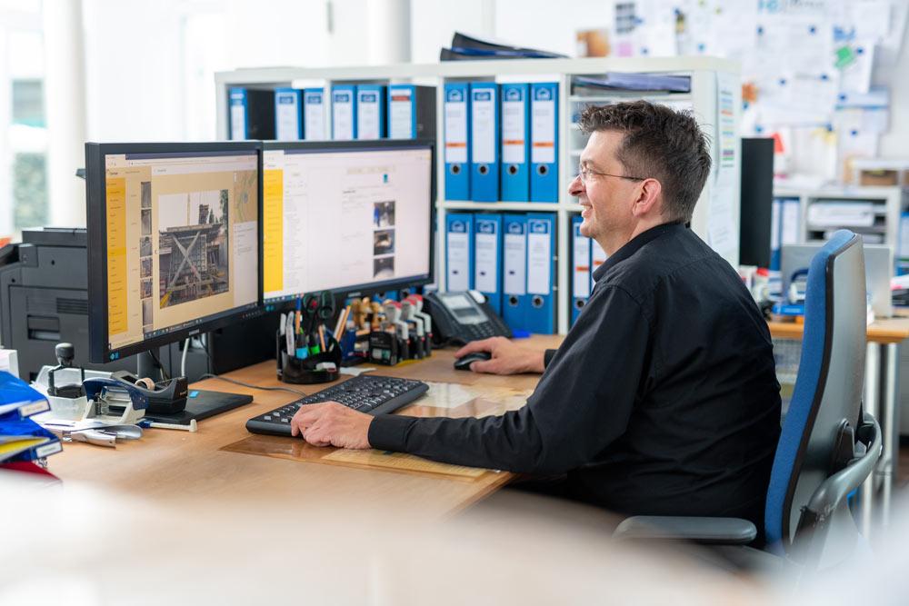 Mitarbeiter einer Bauunternehmens nutzt das digitale Bautagebuch im Büro