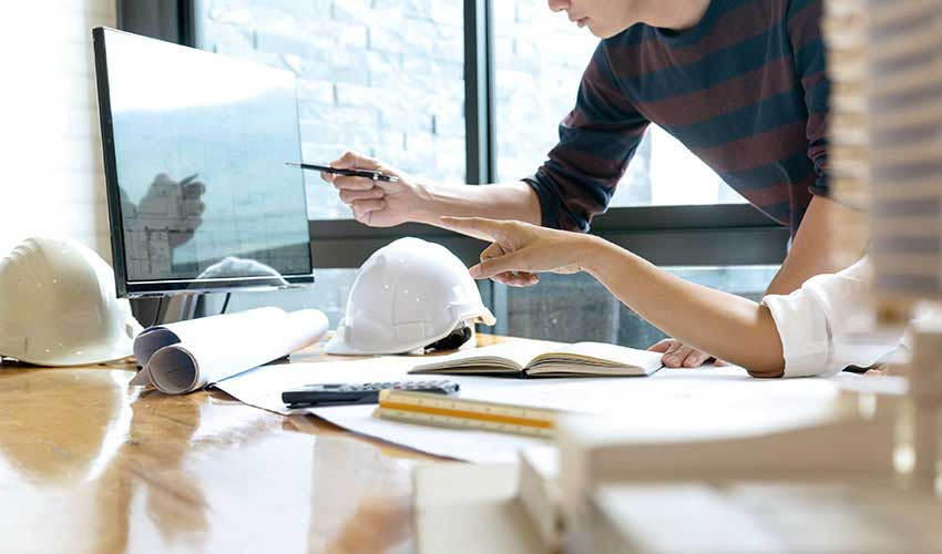 Zwei Mitarbeiter in einem Bauunternehmen diskutieren vor großem Bildschirm.