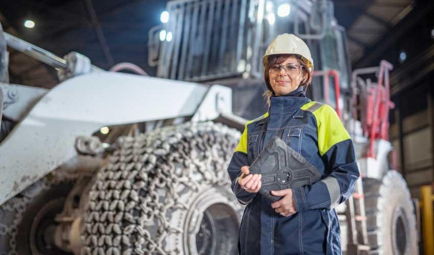 Eine Bauarbeiterin steht mit einem Tablet in der Hand vor einem großen Bagger.