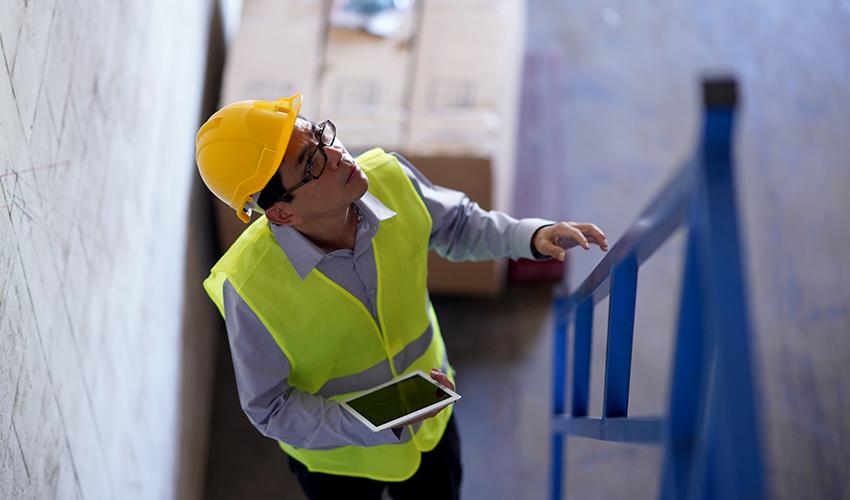 Mann mit Bauhelm, Warnweste und Tablet steigt eine Bautreppe hoch