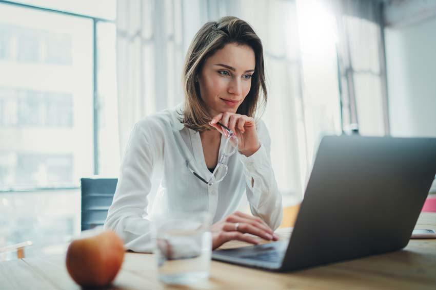 Frau sitzt vor dem Laptop mit einem Apfel und einem Wasserglas