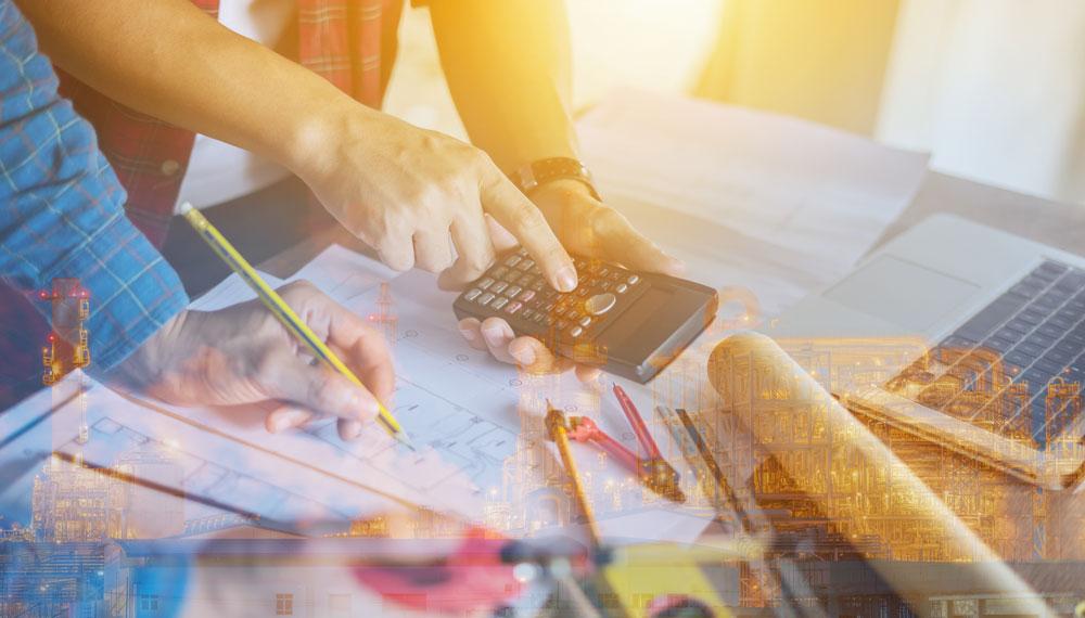 Schreibtisch mit Grundrissplänen, Taschenrechner und Zirkel
